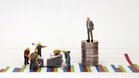 Photo pour A man dressed in a suit standing on top of a pile of coins against a graph and miniature workers at a construction site below it. - image libre de droit