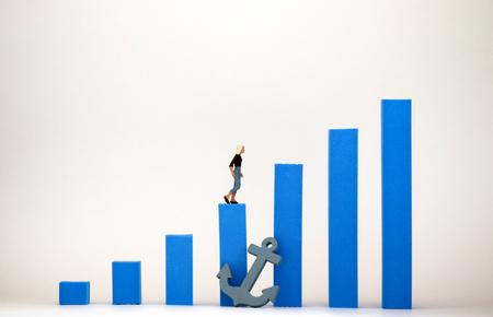 Foto de Blue bar graph and miniature woman. Social environment concept that makes it difficult for women to be promoted. - Imagen libre de derechos