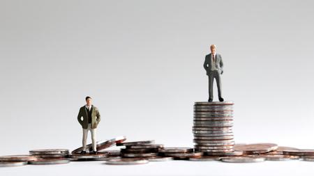Foto de Miniature people standing on a pile of coins. - Imagen libre de derechos