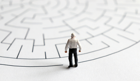 Photo for A miniature man is standing at the entrance to the maze. - Royalty Free Image