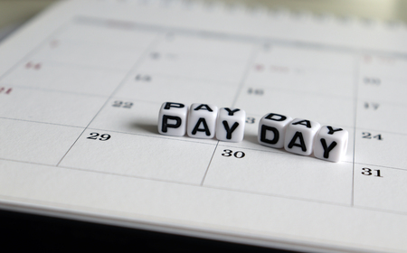 Photo for A white cube arranged in the word 'PAY DAY' on the calendar. - Royalty Free Image