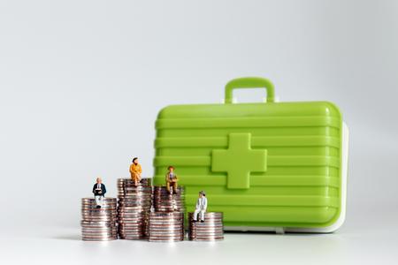 Foto de Old age miniatures sitting on a pile of coins with a medical kit. - Imagen libre de derechos