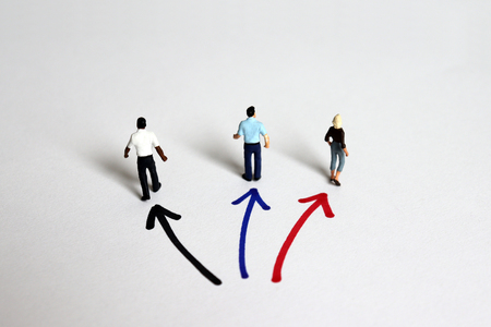 Photo for The back of three miniature people standing in three directions. - Royalty Free Image