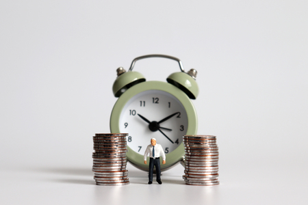Foto de Miniature old man standing with a pile of coins in front of the alarm clock. - Imagen libre de derechos