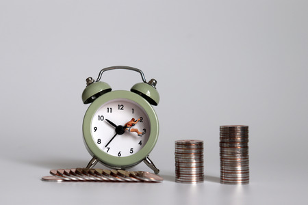 Photo for Miniature people and coins hanging on the clock hands. - Royalty Free Image