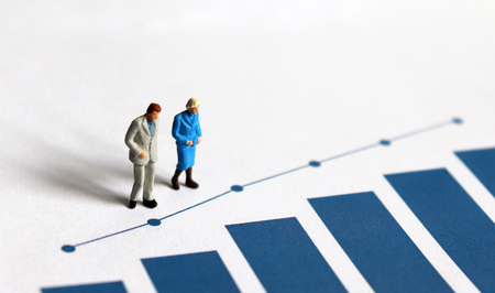 Photo pour A miniature older people standing on a blue bar graph. - image libre de droit
