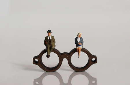 Photo pour Miniature people and miniature glasses. The concept of stereotypes about masculinity and femininity demanded by society. - image libre de droit