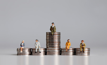 Photo pour Miniature people with stack of coins. A notion of economic inequality. - image libre de droit