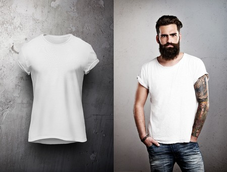 Foto de Bearded man and white tshirt on grey back ground - Imagen libre de derechos