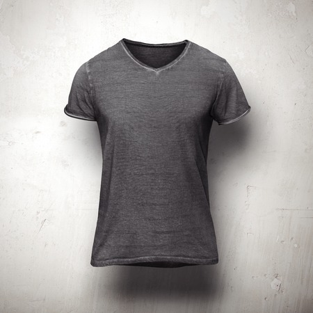 Foto de Dark grey t-shirt isolated on grey wall - Imagen libre de derechos