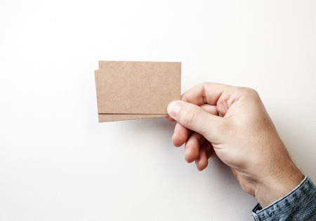 Photo pour Mock up of two blank kraft business cards holding in a hand on the white background - image libre de droit