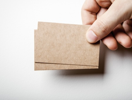 Photo pour Mock up of two blank kraft business cards holding in a mans hand on the white background - image libre de droit