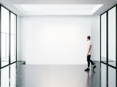 Photo for A man walks on the exhibition hall and examines the gallery of the exhibition - Royalty Free Image