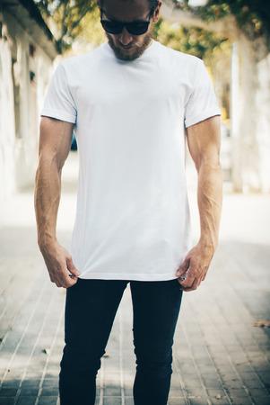 Photo pour Portrait of a bearded guy wearing blank t-shirt, blue jeans, white tshirt and black sunglasses - image libre de droit
