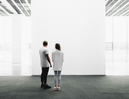 Photo for A man and woman walking through on the exhibition hall and examines the gallery of the exhibition - Royalty Free Image