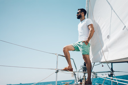 Photo pour Low angle view of young bearded man standing on the nose yacht. Horizontal mockup - image libre de droit