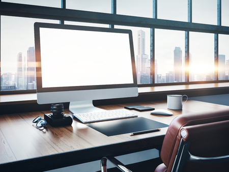 Foto de Photo of generic design computer screen and workspace in loft with panoramic windows and city on the background - Imagen libre de derechos