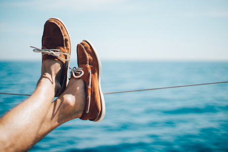 Photo pour Photo of man legs on the yacht and wearing boat shoes. Horizontal mockup - image libre de droit