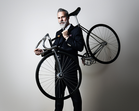 Photo pour Portrait of a handsome middle aged man wearing suit and holding his classic bicycle on the shoulder. Horizontal - image libre de droit
