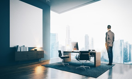 Photo pour Businessman wearing modern suit and looking at the city in contemporary office. Workspace in loft with big white canvas - image libre de droit