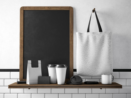 Photo pour Black chalkboard on bookshelf with two blank coffee cups, businesscards, coffee pocket and white holding cotton bag. Horizontal - image libre de droit