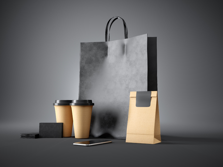 Foto de Set of black shopping bag, two coffee cups, craft package, black business cards and generic design smartphone. Dark background - Imagen libre de derechos