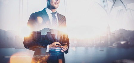 Photo pour Photo of businessman holding smartphone. Double exposure photo of panoramic city view at sunrise - image libre de droit