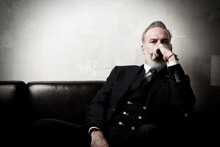 Foto de Portrait of adult businessman wearing trendy suit and sitting modern studio on leather sofa against the empty wall. - Imagen libre de derechos