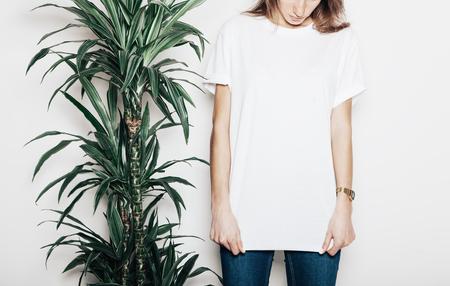 Photo pour Young girl wearing blank t-shirt. Concrete wall background - image libre de droit