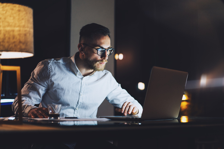Photo for Bearded young businessman wearing white shirt working on modern loft office at night. Man using contemporary notebook texting message, blurred background. - Royalty Free Image