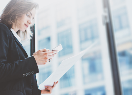 Photo for Pbusiness woman wearing suit, looking smartphone and holding documents in hands. Open space loft office. Panoramic windows background - Royalty Free Image