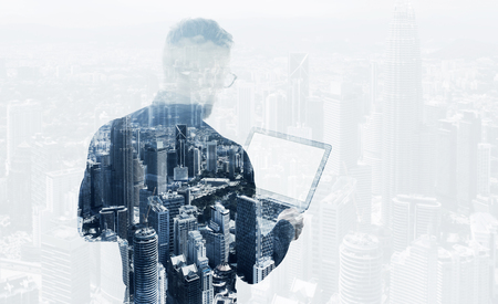 Double exposure young bearded businessman wearing black shirt holding contemporary notebook. Modern megalopolis background. Blank screen ready for your business message.