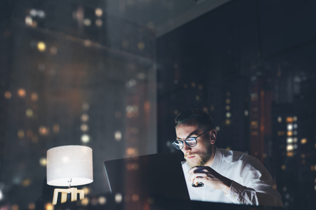 Foto de Bearded young businessman working on modern loft office at night. Man using contemporary notebook texting message, holding cup espresso, blurred background, bokeh - Imagen libre de derechos