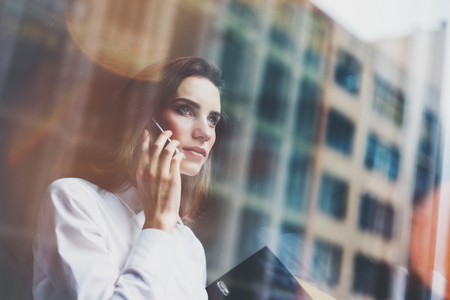 Photo pour Photo business woman wearing modern white shirt, talking smartphone and holding documents in hands. Open space loft office. Panoramic windows background. Horizontal mockup. - image libre de droit