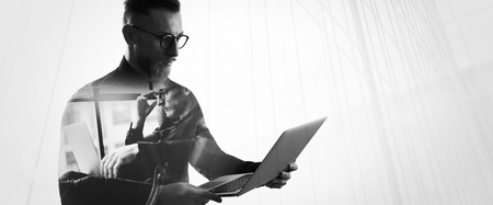 Double exposure bearded businessman wearing shirt and glasses,holding contemporary notebook hands. Portrait young banker using laptop in modern office, skyscraper background.