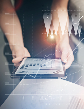 Foto de Photo female hands holding modern tablet. Manager working new private banking project office. Using electronic devices. Graphics icons, worldwide stock exchanges interface on screen. - Imagen libre de derechos