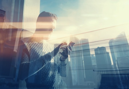 Foto de Double exposure photo man touching screen smartphone.Picture bearded trader manager in modern office panoramic view.Contemporary city skyscrapers background. Film and bokeh effect. - Imagen libre de derechos