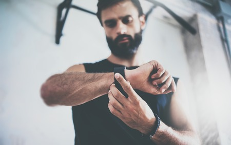 Photo pour Close-up Shot Young Bearded Sportive Man After Workout Session Checks Fitness Results Smart Watch.Adult Guy Wears Sport Tracker Wristband Arm.Training hard gym.Horizontal bar background.Blurred - image libre de droit