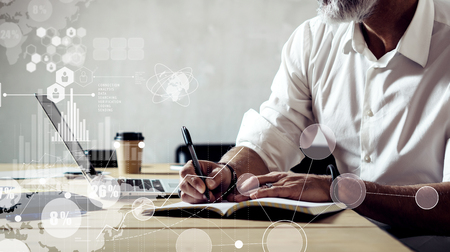 Foto de Concept of digital screen with global virtual icon,diagram, graph interfaces.Adult successful businessman wearing a classic glasses and working on laptop at the wood table in modern loft.Wide - Imagen libre de derechos