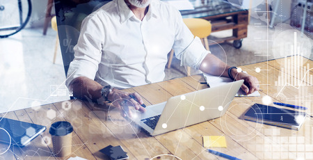 Photo pour Concept of digital screen with virtual icon,diagram, graph and interfaces.Stylish bearded middle age man using laptop on workplace. Horizontal wide, blurred background - image libre de droit