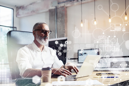 Photo for Concept of digital screen,virtual icon,diagram, graph and interfaces.Middle age financial analyst wearing a classic glasses and working at the wood table with exchange markets.Horizontal - Royalty Free Image