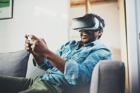 Foto de Smiling african man enjoying virtual reality glasses while sitting on sofa.Happy young guy with vr headset or 3d spectacles and controller gamepad playing video game at home.Blurred. - Imagen libre de derechos