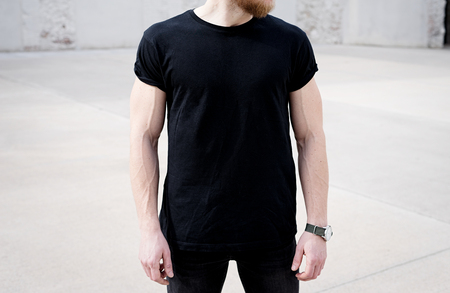 Photo pour Young muscular bearded man wearing black tshirt and jeans posing in center of modern city. Empty concrete wall on the background. Hotizontal mockup, front view - image libre de droit