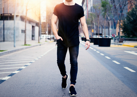 Foto de Young muscular man wearing black tshirt and jeans walking on the streets of the modern city. Blurred background. Hotizontal mockup. - Imagen libre de derechos