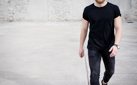 Photo pour Young muscular man wearing black tshirt and jeans walking on the urban district. Blurred background. Hotizontal mockup. - image libre de droit