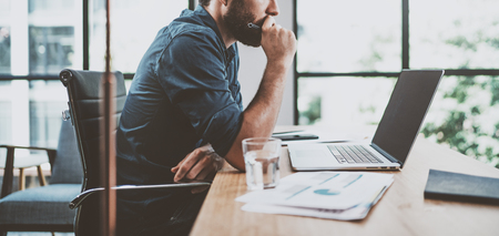 Photo for Young pensive coworker working at sunny work place loft while sitting at the wooden table.Man analyze document on laptop display.Blurred background.Horizontal wide. - Royalty Free Image