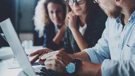 Foto de Concept of teamwork process at office.Young team working together at night modern office loft.Blurred background.Horizontal.Cropped. - Imagen libre de derechos