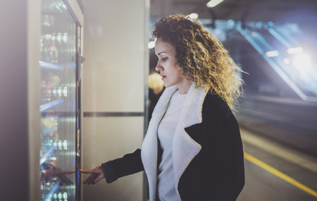 Photo pour Attractive woman on transit platform using a modern beverage vending machine.Her hand is placed on the dial pad and she is looking on the small display screen. - image libre de droit