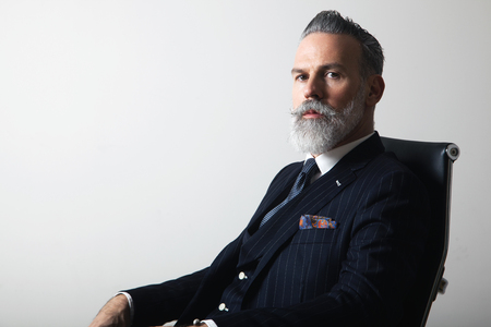 Foto de Portrait of positive bearded middle aged gentleman wearing trendy suit over empty gray background. Copy Paste space. Studio shot - Imagen libre de derechos