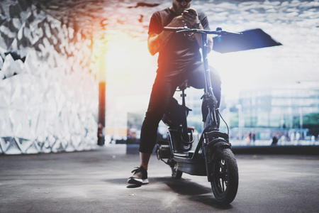 Foto de Bearded tattooed male in sunglasses using smartphone after riding by electric scooter in the city. - Imagen libre de derechos